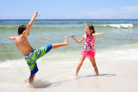 family fight: Energetic little children fighting on beach at sea