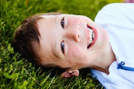 Close-up of little boys happy face lying on grass