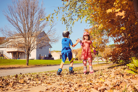 skate park: Happy little kids roller skating and giving five