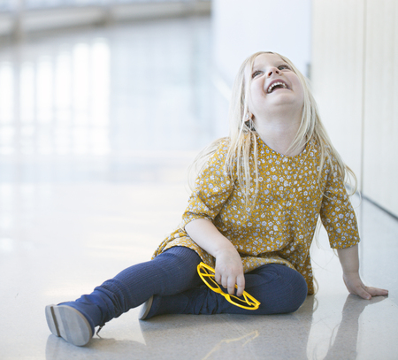 Portrait of happy little girl sitting on wall and laughing