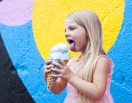 Beautiful blond girl holding ice-cream on colorful background
