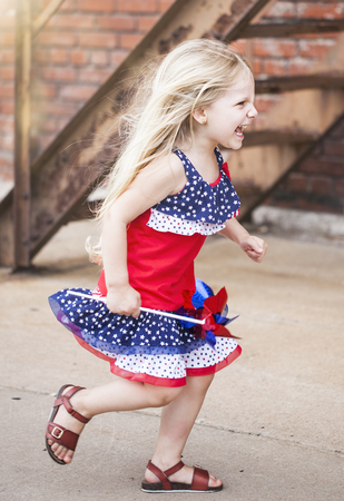Portrait of active little girl running outdoors. Cute Caucasian girl wearing stars and stripes dress walking on street. Independence day