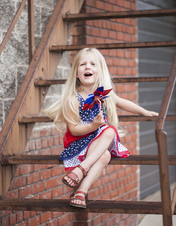 Cute little girl with pinwheel sitting on stairs with open mouth. Portrait of blond girl wearing stars and stripes dress. Independence day