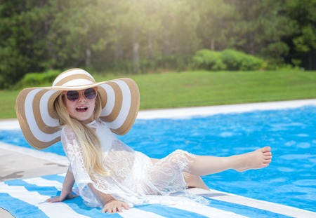 Cheerful little girl with hat sitting next to swimming pool Stok Fotoğraf