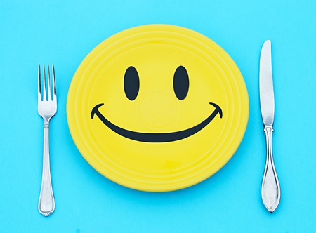 Yellow plate with smile and cutlery on blue background