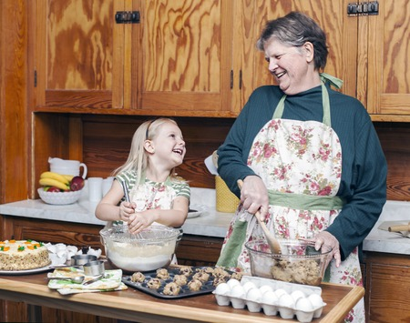 Happy grandmother and granddaughter cooking together and having fun in the kitchen
