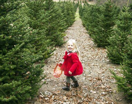 Portrait of happy little girl walking with lantern among fir trees. Girl wearing red coat walking in winter