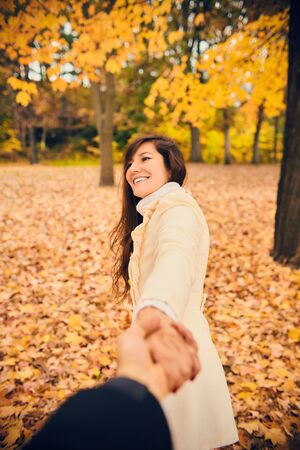 Portrait of happy young woman holding hand and dragging friend in autumn park. Cheerful girl walking with boyfriend at fall. Season, friendship, dating