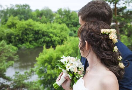 Rear view of young married couple looking together at view. Bride standing at broom and holding wedding bouquet. Newlywed standing at river. Wedding, marriage, romance 写真素材