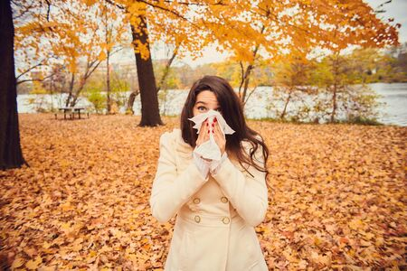 Portrait of young woman blowing nose in autumn park. Girl holding tissue, sneezing or coughing. Cold, flu, allergy