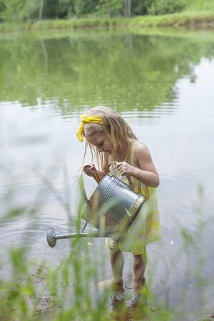Concentrated little girl standing in lake with watering can. Lovely child playing in summer. Childhood, vacations, leisure 版權商用圖片