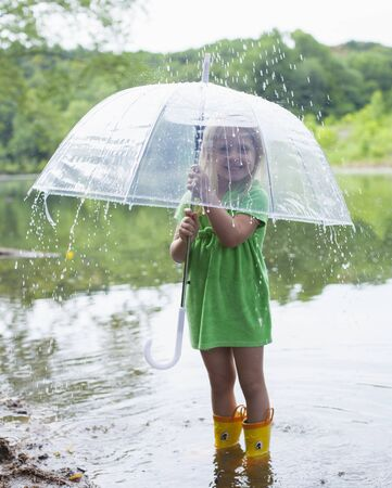 Portrait of happy little girl standing in river with umbrella in rain. Lovely child wearing green dress and rubber boots. Summer, autumn, environment 版權商用圖片