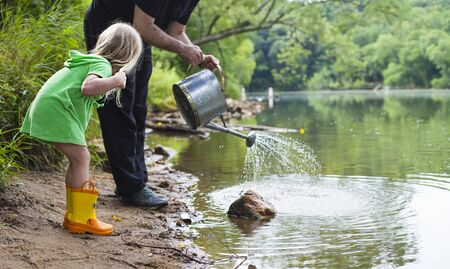 Little girl standing with father at lake shore. Man holding watering can, daughter looking at him. Family, vacation, summer