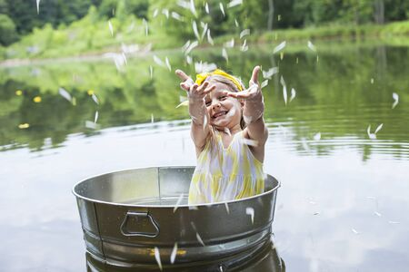 Portrait of laughing little girl splashing in tub amid lake. Cute child throwing petals outside and having fun. Summer, childhood, vacations