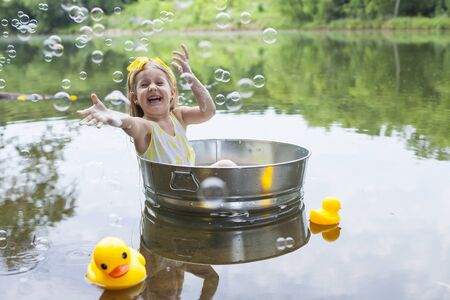 Cheerful little girl floating in tub amid lake with rubber ducks. Happy kid enjoying soap sud outside. Summer, childhood, vacations 版權商用圖片