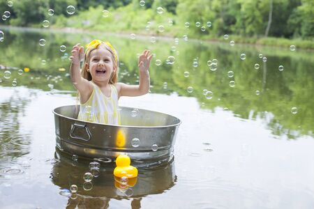 Excited little girl enjoying soap sud at lake. Happy kid sitting in metal tub in summer. Summer, childhood, vacations