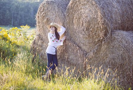 Smiling young girl posing at hay bales. Farm girl wearing blouse, cowboy hat and western boots standing in field. Countryside, farming, agriculture Banque d'images