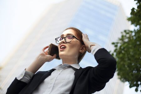 Stressed young businesswoman talking to her boss on mobile phone. Close-up of redhead female manager talking on smartphone in fear 스톡 콘텐츠