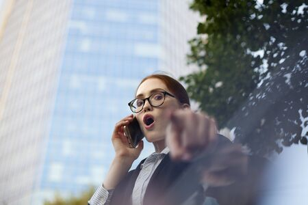 Excited businesswoman talking on mobile phone and pointing at camera. Portrait of female manager wearing glasses using smartphone pointing at you Stock Photo