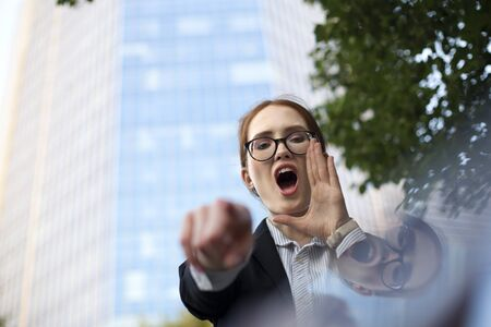 Portrait of excited manager shouting and pointing at camera. Young businesswoman wearing glasses advertising something at office building