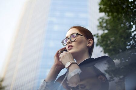 Anxious young businesswoman talking on mobile phone. Face of redhead female manager wearing glasses calling up partner outdoors Фото со стока
