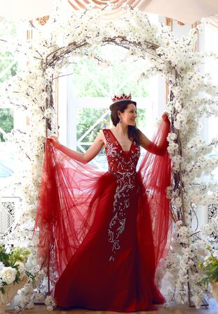 Portrait of happy young woman wearing red evening dress and tiara posing in arc with flowers. Pretty woman standing against window in studio