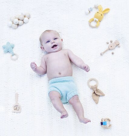 Smiling little baby lying in blue panties in bed with rattles. Portrait happy baby boy resting on cradle. Newborn child, childhood