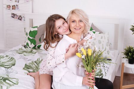 Portrait of smiling woman and her daughter at Mother s Day. Teenage girl sitting on bed and embracing her mother with flowers. Family, holiday, motherhood