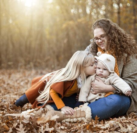 Portrait of happy family with mother and two little children outdoors. Young mother sitting with daughter and son on foliage, little girl kissing her baby brother. Motherhood, family, weekend