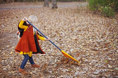 Little girl removing leaves with broom. Child wearing coat working in autumn garden. Childhood, fall, chores