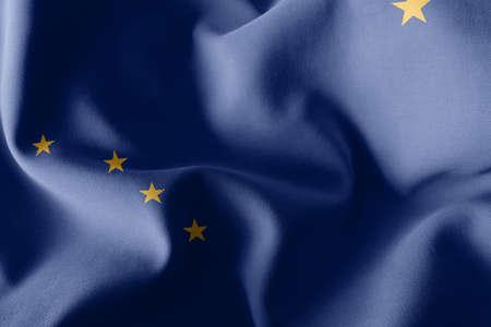 3D illustration flag of Alaska is a region of United States. Waving on the wind flag textile background