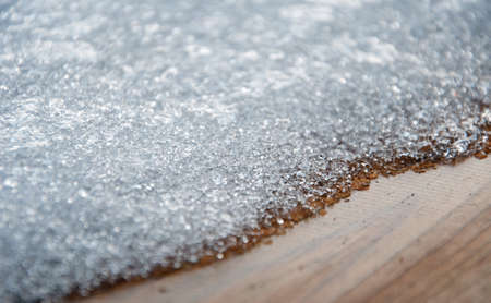 graining: Snow cristals melting on a wood decking Stock Photo