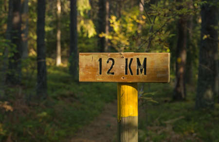 wooden trail sign: A wooden sign indicating the distance twelve kilometers Stock Photo