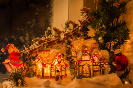 pulled over: Santa driving his sleigh pulled by reindeer over a lighted house