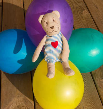 balloons teddy bear: teddy bear sits on five balloons in different colors