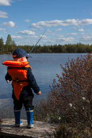 life jacket: Young boy is fishing wiht his rod wearing life jacket by the lake