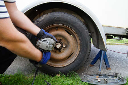 unscrewing: Brake Repair unscrewing whee wiht powertool.