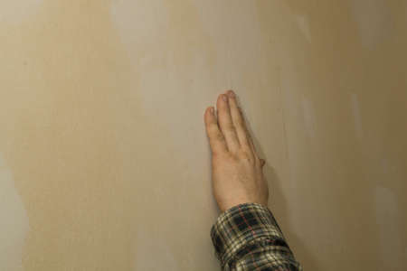 fillers: A man is making the necessary ground job for wallpapering a room.