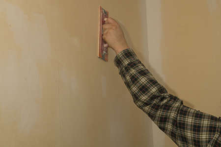 feel feeling: A man is making the necessary ground job for wallpapering a room.