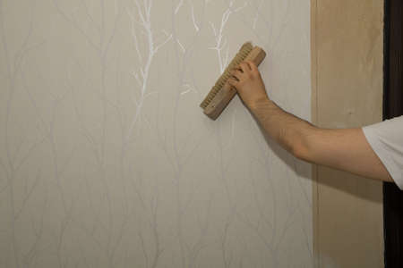 preparatory: A man is making the necessary ground job for wallpapering a room.