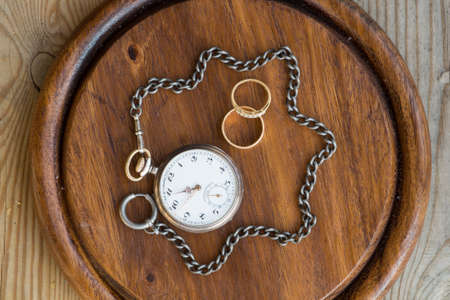 togheter: A pocket watch which chain encircles a couple of rings representing how time strenthens love and binds people togheter.