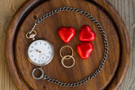 dial plate: A pocket watch which chain encircles a couple of rings representing how time strenthens love and binds people togheter.