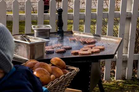 sizzling: Chef cooking on his outdoor kitchen hamburger sizzling on a frying table while customers a waiting in line.