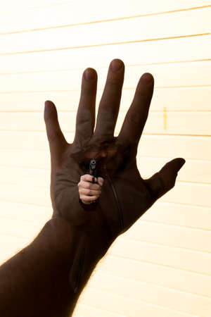 life threatening: A multi exposure image of a hand held up to try to stop a robber who point at the man with his gun.