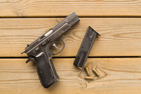 mag: A modern pistol 9 millimeter parabellum on a wooden deck and with magazine