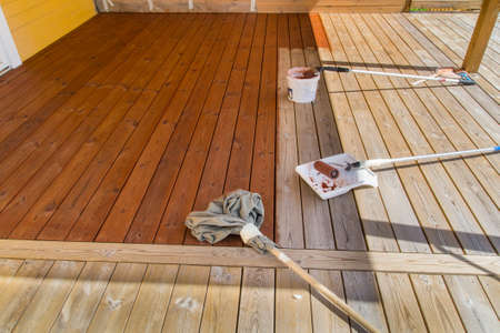 oiled: Painting the porch with pigmented oil half way finished with tools visible on the wooden deck.