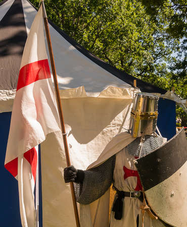 role play: A person dresses up historically to mimic a knights templar in full armour standing in front of a white and blue tent holding a shield and flag.