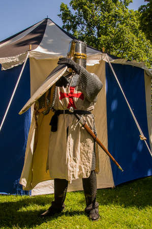 A person dressed up historically to mimic a knights templar in full armour  standing in front of a white and blue tent grabbing a shield. Stock Photo