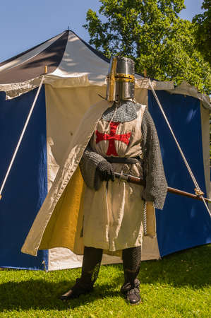 historically: A person dressed up historically to mimic a knights templar in full armour standing in front of a white and blue tent.