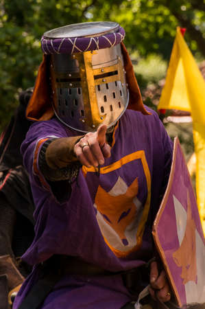 role play: A person dresses up historically to mimic a knight in full armour with purple clothing, pointing towards the camera Stock Photo